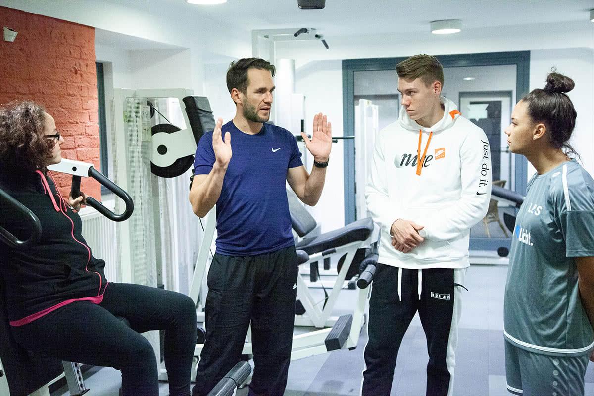 Lehrer mit Schülern im Fitnessraum