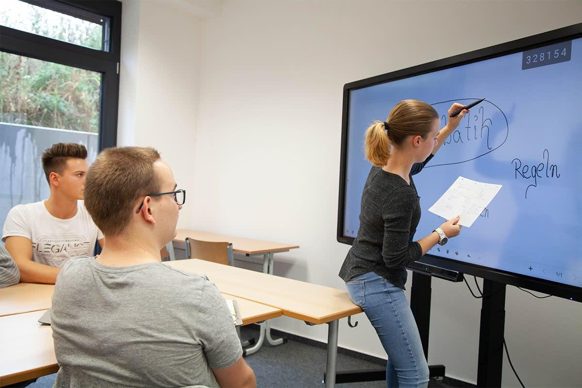 Lehrerin an digitaler Tafel am unterrichten